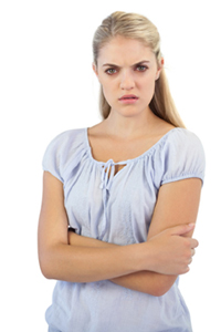 Outraged blonde woman  with arms crossed on white background