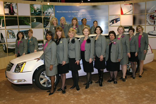 Kathy Mills, in front of the pink Cadillac, third from left, once had a strong Mary Kay network. Here she is with her group of directors.