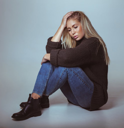 Pensive Woman In Sweater Sitting On Floor