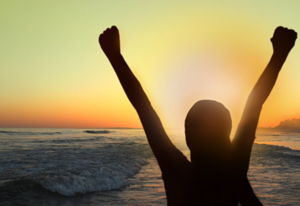 Woman with arms raised at sunset on the beach